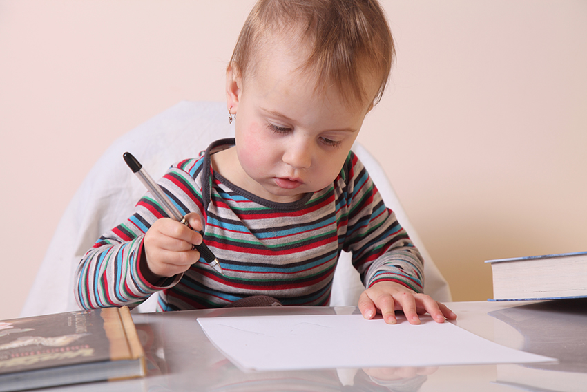 Photo of a baby with pen and paper